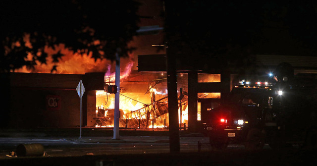 A fire is seen Sunday, Aug. 10, 2014, in Ferguson, Mo. A few thousand people crammed a suburban St. Louis street Sunday night at a vigil for unarmed 18-year-old Michael Brown shot and killed by a  ...