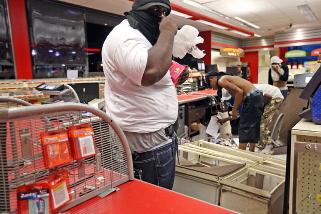 People are seen in a store Sunday, Aug. 10, 2014, in Ferguson, Mo. A few thousand people crammed a suburban St. Louis street Sunday night at a vigil for unarmed 18-year-old Michael Brown shot and  ...
