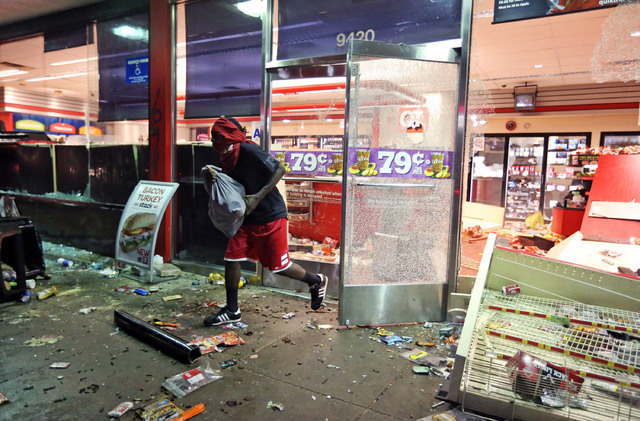 A man leaves a store on Sunday, Aug. 10, 2014, in Ferguson, Mo. A few thousand people crammed a suburban St. Louis street Sunday night at a vigil for unarmed 18-year-old Michael Brown shot and kil ...