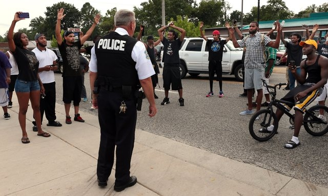 Protestors blocking Florissant Road raise their hands after being approached by police officers who asked them to stop blocking the street in front of the Ferguson police department on Sunday, Aug ...