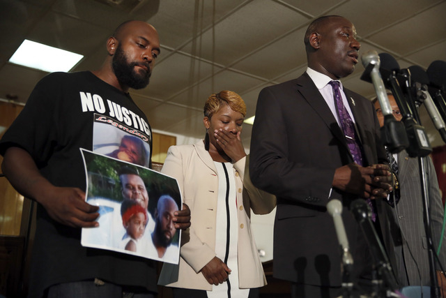 Lesley McSpadden, center, and Michael Brown Sr., left, the parents of Michael Brown, listen as attorney Benjamin Crump speaks during a news conference Monday, Aug. 11, 2014, in Jennings, Mo. Micha ...