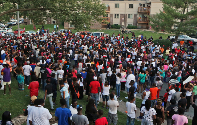 A large crowd gathers at the candlelight vigil, Sunday evening, Aug. 10, 2014, in Ferguson, Mo. A few thousand people have crammed the street where a black man was shot multiple times by a suburba ...
