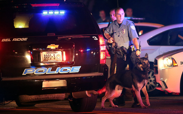 Police officers patrol the area Sunday, Aug. 10, 2014, in Ferguson, Mo. A few thousand people crammed a suburban St. Louis street Sunday night at a vigil for unarmed 18-year-old Michael Brown shot ...