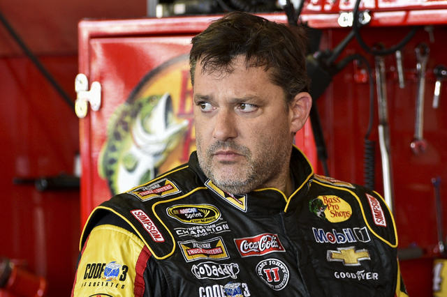 Tony Stewart stands in the garage area on Friday, Aug. 8, 2014, after a practice session for Sunday's NASCAR Sprint Cup Series auto race at Watkins Glen International, in Watkins Glen N.Y. (AP Pho ...