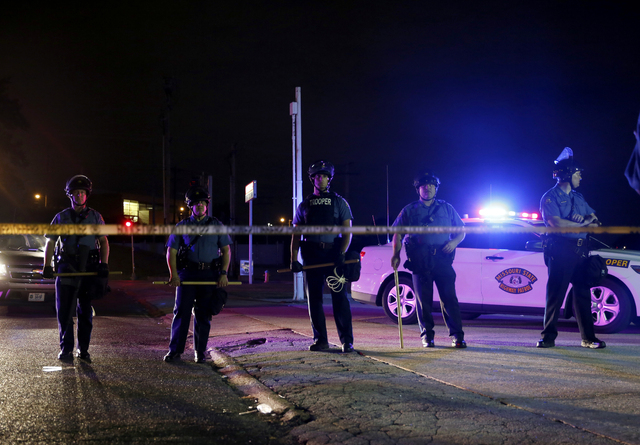 Police wearing riot gear try to disperse a crowd Monday, Aug. 11, 2014, in Ferguson, Mo. Authorities in Ferguson used tear gas and rubber bullets to try to disperse a large crowd Monday night that ...