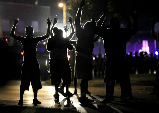 People raise their hands in the middle of the street as police wearing riot gear move toward their position trying to get them to disperse Monday, Aug. 11, 2014, in Ferguson, Mo. The FBI opened an ...