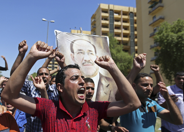 Iraqis chant pro-government slogans and display placards bearing a picture of embattled Prime Minister Nouri al-Maliki during a demonstration in Baghdad, Iraq, Monday, Aug. 11, 2014. Al-Maliki is  ...