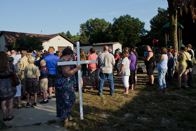 A woman carries a cross to a memorial during a vigil for Michael Connor Verkerke, 9, who was stabbed and killed Monday, Aug. 4, by a 12 year-old-boy, who is currently facing a murder charge, in Ke ...