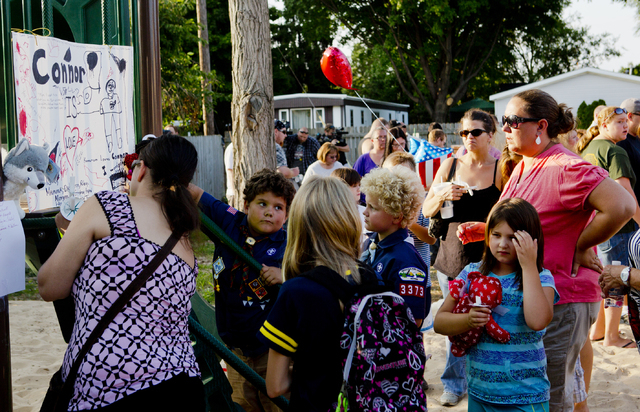 Community members write their thoughts on a memorial dedicated  to Michael Connor Verkerke, 9, who was stabbed and killed Monday, Aug. 4, by a 12 year-old-boy, who is currently facing a murder cha ...