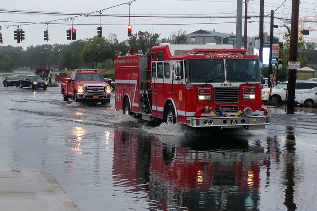 Firefighters cross a flooded intersection on Route 110 in Farmingdale, N.Y., on New York's Long Island, Wednesday, Aug. 13, 2014. Stranded Long Island drivers have been rescued after a storm slamm ...