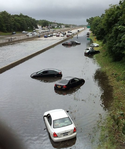 Vehicles are submerged on a flooded section of Sunrise Highway, in East Islip, N.Y., on New York's Long Island, Wednesday Aug. 13, 2014. Stranded Long Island drivers have been rescued after a stor ...