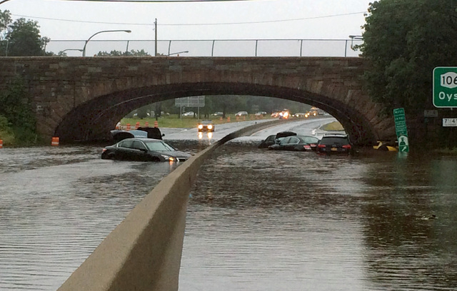 Vehicles are submerged on a flooded section of the Northern State Parkway, near Route 107, in Jericho, N.Y., on New York's Long Island, Wednesday Aug. 13, 2014. Stranded Long Island drivers have b ...