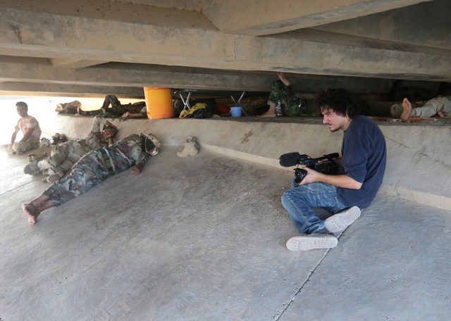 This July 1, 2014 photo shows Associated Press video journalist Simone Camilli at work filming Kurdish Peshmerga fighters under a bridge near the front line with militants from the Islamic state g ...