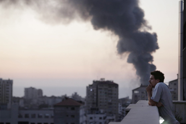 This photo taken in August, 2014 shows Associated Press video journalist Simone Camilli on a balcony overlooking smoke from Israeli Strikes in Gaza City. Camilli, 35, was killed in an ordnance exp ...