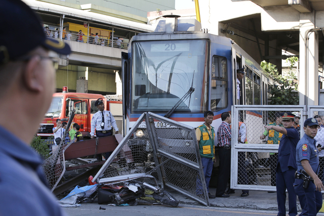 Police cordon off the area after an elevated commuter train known as Metro Rail Transit overshot its tracks and derailed at the end station Wednesday, Aug. 13, 2014, injuring dozens at suburban Pa ...