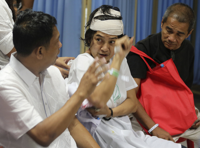 Filipinos who were among those injured in a commuter train accident talk while inside the emergency room of the San Juan de Dios hospital in suburban Pasay, Philippines, on Wednesday, Aug. 13, 201 ...