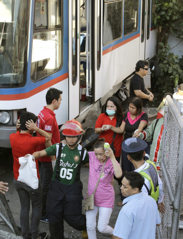 Rescuers rush injured passengers to a hospital after an elevated commuter train known as Metro Rail Transit overshot its tracks and derailed at the end station Wednesday, Aug.13, 2014, injuring do ...