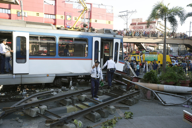 Train guards gather at the site of an elevated commuter train known as Metro Rail Transit after it overshot its tracks and derailed at the end station Wednesday, Aug. 13, 2014, injuring dozens in  ...