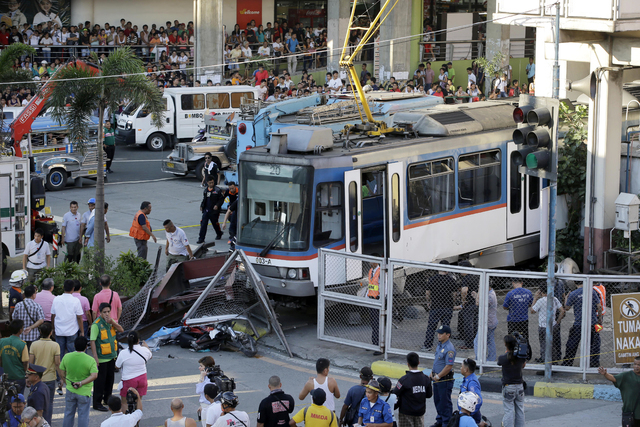 Rescuers and onlookers gather around the wreckage of an elevated commuter train known as Metro Rail Transit after it overshot its tracks and derailed at the end station Wednesday, Aug. 13, 2014, i ...