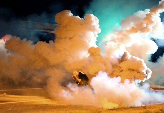 A protester takes shelter from smoke billowing around him Wednesday, Aug. 13, 2014, in Freguson, Mo. Protests in the St. Louis suburb rocked by racial unrest since a white police officer shot an u ...