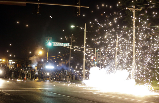 A device deployed by police goes off in the street as police and protesters clash Wednesday, Aug. 13, 2014, in Ferguson, Mo. Authorities in the St. Louis suburb where an unarmed black teen was sho ...