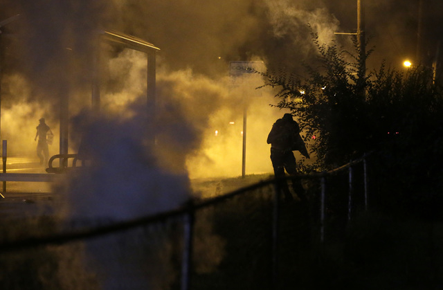 A person runs through smoke Wednesday, Aug. 13, 2014, in Ferguson, Mo.  Protests in the St. Louis suburb rocked by racial unrest since a white police officer shot an unarmed black teenager to deat ...