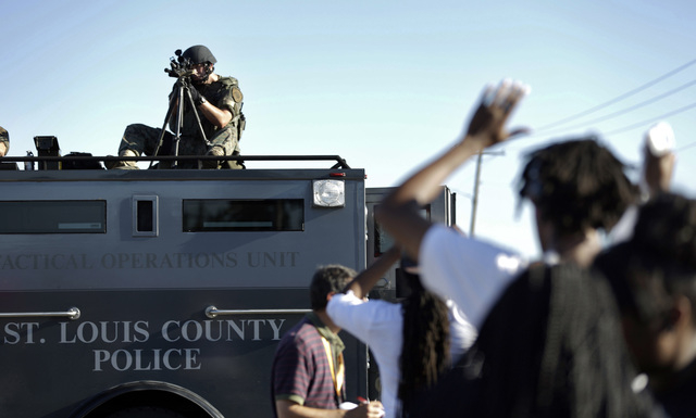 A member of the St. Louis County Police Department points his weapon in the direction of a group of protesters in Ferguson, Mo. on Wednesday, Aug. 13, 2014. On Saturday, Aug. 9, 2014, a white poli ...