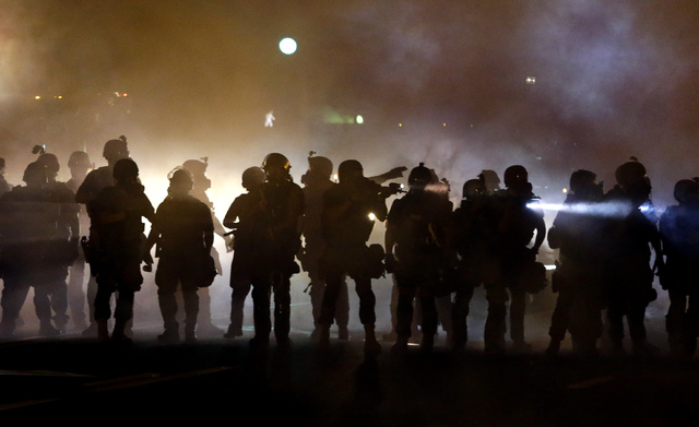 Police walk through a cloud of smoke as they clash with protesters Wednesday, Aug. 13, 2014, in Ferguson, Mo.  Protests in the St. Louis suburb rocked by racial unrest since a white police officer ...