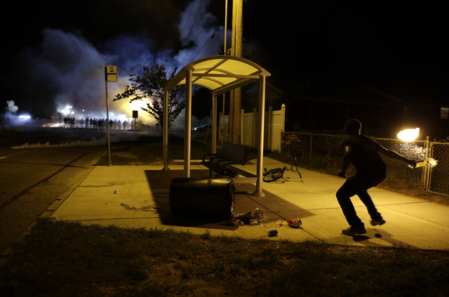 A man picks up a flaming bottle and prepares to throw it as a line of police advance in the distance Wednesday, Aug. 13, 2014, in Ferguson, Mo. Authorities the St. Louis suburb where an unarmed bl ...