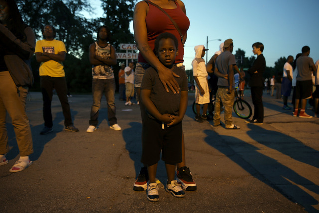 Jeremiah Parker, 4, stands in front of his mother, Shatara Parker, as they attend a protest Wednesday, Aug. 13, 2014, in Ferguson, Mo. Nights of unrest have vied with calls for calm in a St. Louis ...
