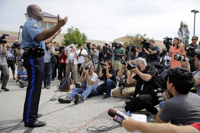 Capt. Ron Johnson of the Missouri Highway Patrol, left, speaks during a news conference Friday, Aug. 15, 2014, in Ferguson, Mo. Missouri Gov. Jay Nixon assigned protest oversight to Johnson after  ...