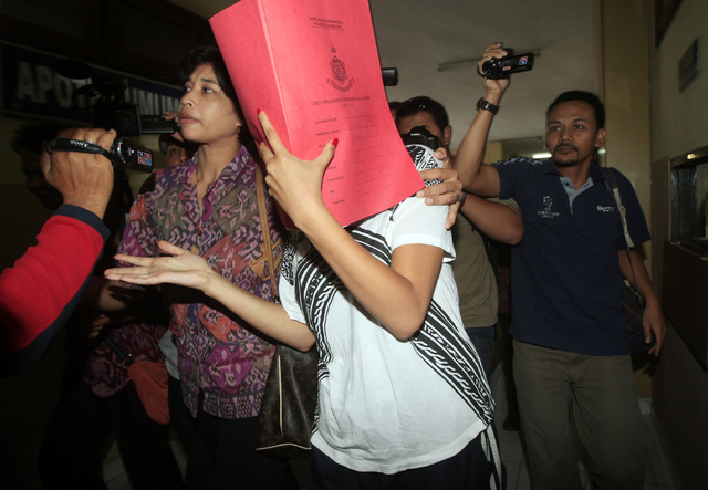 Heather Mack, covering her face, is led to a hospital for a medical check by Indonesian police officers in relation to the death of her mother Sheila von Wiese-Mack in Bali, Indonesia, Friday, Aug ...