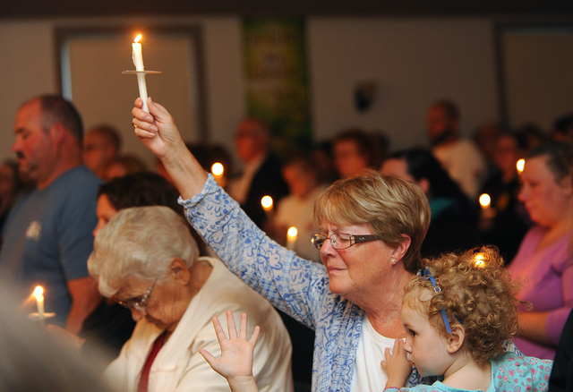 Lillian LaRose of Heuvelton, N.Y., holds up a candle on Thursday, Aug. 14, 2014, during a candlelight vigil at the Cornerstone Wesleyan Church in Heuvelton for Fannie Miller, 12, and her sister De ...