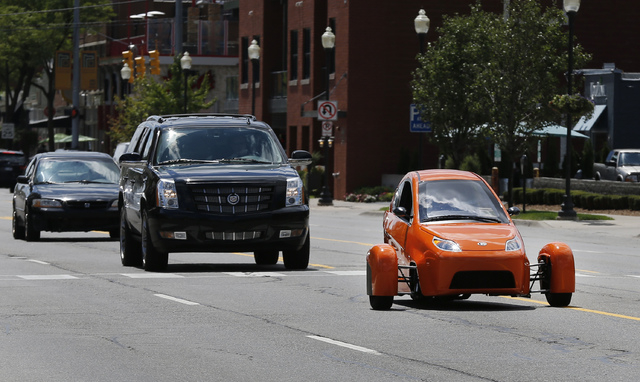 The Elio, a three-wheeled prototype vehicle, is shown in traffic in Royal Oak, Mich., Thursday, Aug. 14, 2014. Instead of spending $20,000 on a new car, Paul Elio is offering commuters a cheaper o ...