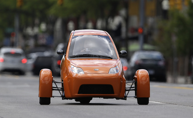 The Elio, a three-wheeled prototype vehicle, is shown in traffic in Royal Oak, Mich., Thursday, Aug. 14, 2014. The vehicle will sell for $6,800 car and can save on gas with fuel economy of 84 mpg. ...