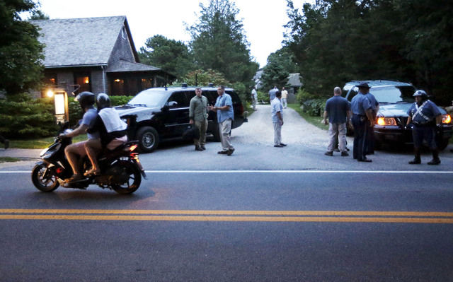 Two people on a motor scooter, left, drive by as law enforcement officials from Secret Service and Massachusetts State Police stand outside State Road Restaurant where President Barack Obama and f ...