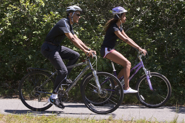 President Barack Obama bike rides with daughter Malia Obama on the Manuel F. Correllus State Forest bike path, Friday, Aug. 15, 2014, outside of West Tisbury, Mass., during the Obama family vacati ...