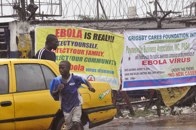 People pass by Ebola virus health warning signs, in the city of Monrovia, Liberia, Sunday, Aug. 17, 2014. Liberian officials fear Ebola could soon spread through the capital's largest slum after r ...
