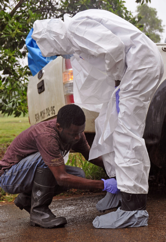 A health worker, left, helps a colleague with his personal protection equipment before dealing with individuals suspected of suffering from the Ebola virus in Monrovia, Liberia, Saturday, Aug. 16, ...