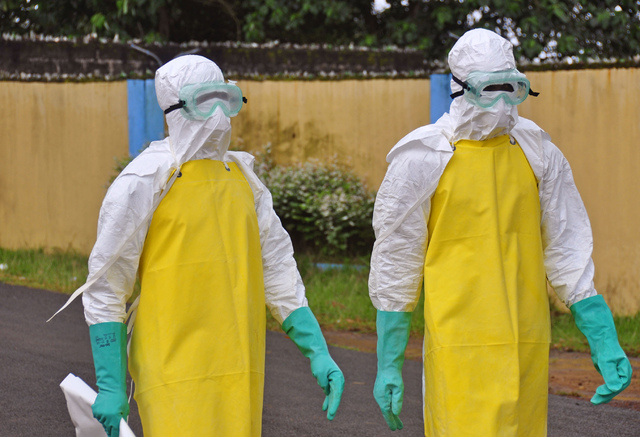 Health workers wearing protective gear go to remove the body of a person who is believed to have died after contracting the Ebola virus in the city of Monrovia, Liberia, Saturday, Aug. 16, 2014. N ...