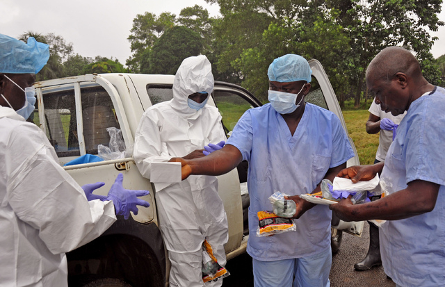 Health workers are handed personal protective gear by a team leader, right, before collecting the bodies of the deceased from streets in Monrovia, Liberia, Saturday, Aug. 16, 2014. New figures rel ...