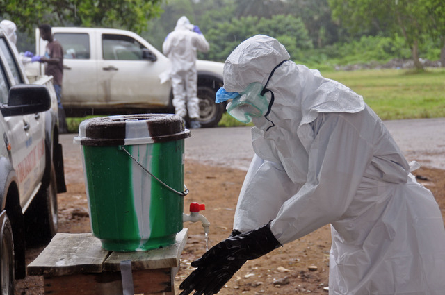 A health worker washes with disinfectant after dealing with people suspected of having the Ebola virus in the city of Monrovia, Liberia, Saturday, Aug. 16, 2014. New figures released by the World  ...