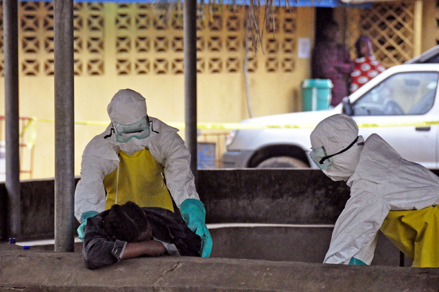 Health workers move the body of a fellow health worker who was found dead in a seat, and who they believe passed away from the Ebola virus, at one of the largest hospitals in the city of Monrovia, ...