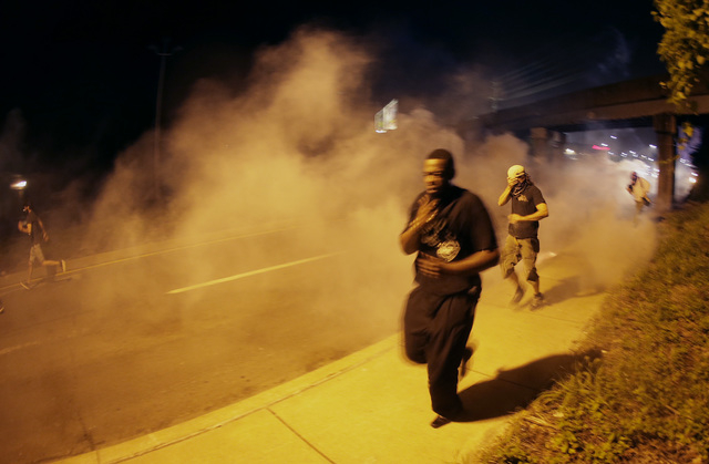People run from tear gas after police dispersed a crowd Sunday, Aug. 17, 2014, as they staged a protest for Michael Brown, who was killed by a police officer last Saturday in Ferguson, Mo. As nigh ...