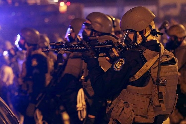 Police advance after tear gas was used to disperse a crowd Sunday, Aug. 17, 2014, during a protest for Michael Brown, who was killed by a police officer last Saturday in Ferguson, Mo. As night fel ...
