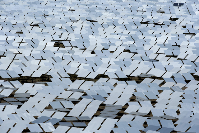 An array of mirror at the Ivanpah Solar Electric Generating System is shown Aug. 13, 2014, near Primm. The site uses over 300,000 mirrors to focus sunlight on boilers' tubes atop 450-foot towers h ...