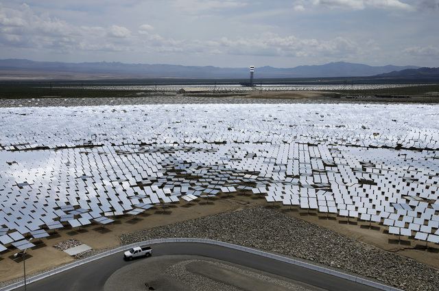 A truck drives by an array of mirrors at the Ivanpah Solar Electric Generating System near Primm on Aug. 13, 2014. The site uses over 300,000 mirrors to focus sunlight on boilers' tubes atop 450 f ...