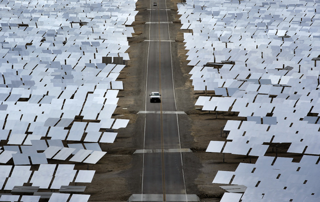 A truck drives through an array of mirrors at the Ivanpah Solar Electric Generating System near Primm on Aug. 13, 2014. The site uses over 300,000 mirrors to focus sunlight on boilers' tubes atop  ...