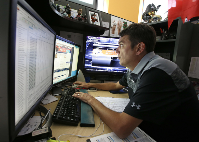In this Wednesday, Aug. 6, 2014 photo, Donny Moore works at three computer screens as he rates NFL football players for the Madden NFL video football game at EA Sports in Orlando, Fla.  Moore is t ...