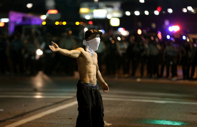 A man stands in the street during a protest Monday, Aug. 18, 2014, for Michael Brown, who was killed by a police officer Aug. 9 in Ferguson, Mo. Brown's shooting has sparked more than a week of pr ...
